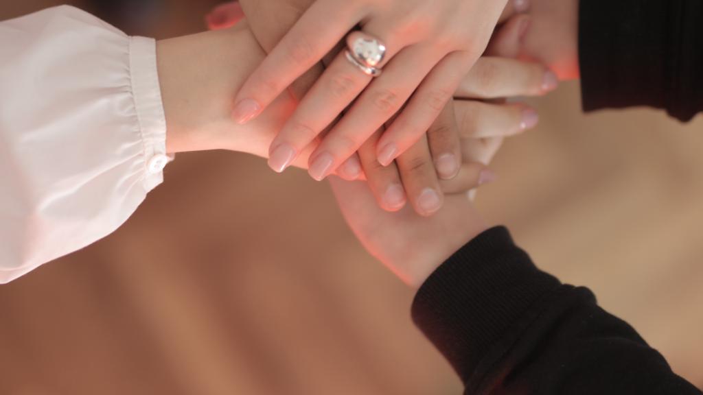 Un gesto di solidarietà, le mani di due donne che si stringono